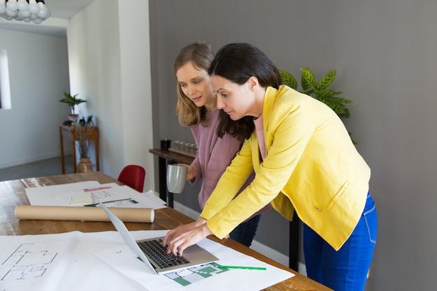 Architetto e cliente femminili contenti che per mezzo del computer portatile Foto Gratuite