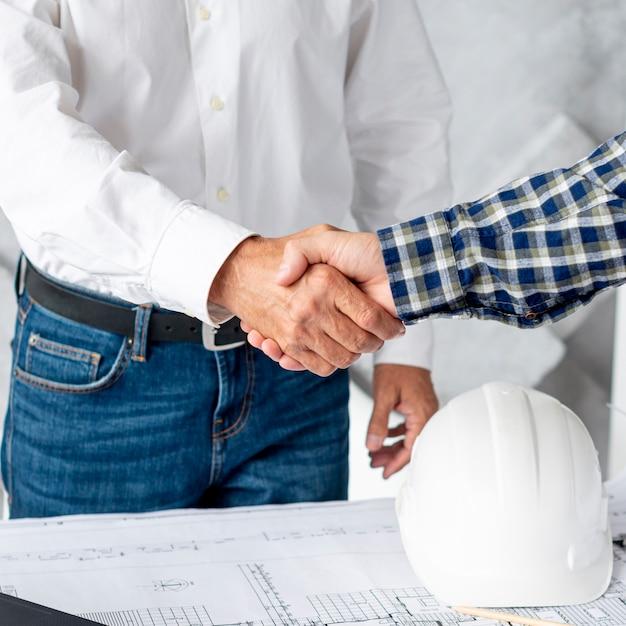 Architetto e cliente stringono la mano Foto Gratuite