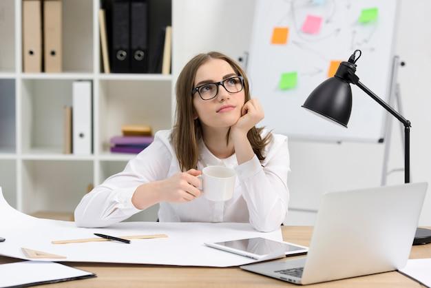 Architetto femminile contemplato che tiene tazza di caffè che si siede nel luogo di lavoro Foto Gratuite