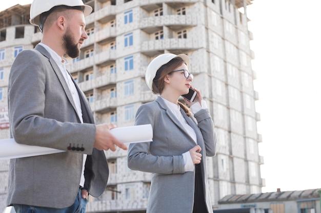 Architetto professionista della donna che parla sul cellulare che sta con il suo collega maschio al cantiere Foto Gratuite