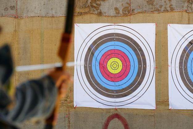 Arciere sta mirando il tiro con l'arco al bersaglio Foto Premium