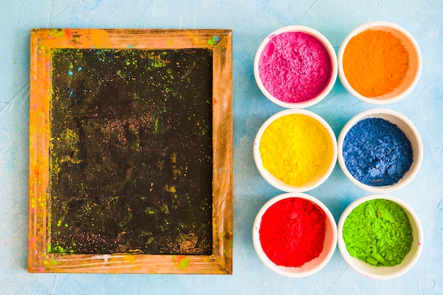 Ardesia di legno disordinato con polvere di colore holi nelle ciotole bianche su sfondo dipinto Foto Gratuite