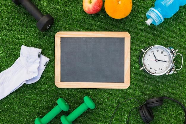 Ardesia di legno vuota con attrezzature sportive e frutta sana sul tappeto erboso verde Foto Gratuite