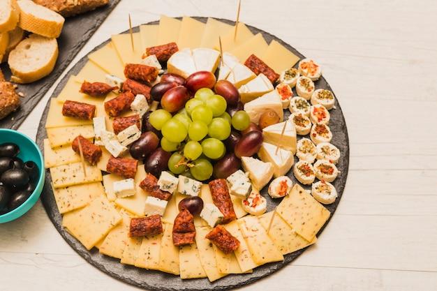 Ardesia nera circolare con piatto di formaggi; uva e salsicce affumicate sul tavolo di legno Foto Gratuite