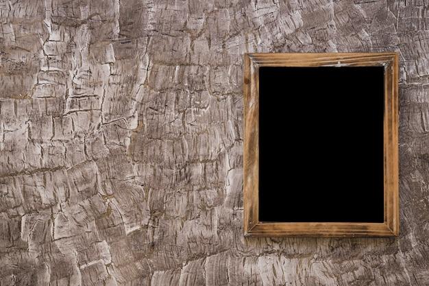 Ardesia nera di legno sul muro Foto Gratuite