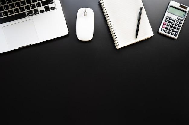 Area di lavoro con calcolatrice, penna, computer portatile, nota sullo sfondo nero. Foto Premium