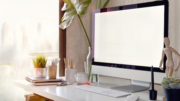 Area di lavoro con computer schermo vuoto su un tavolo bianco Foto Premium