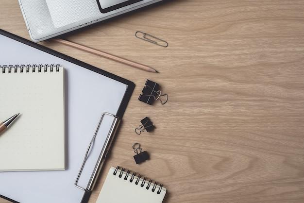 Area di lavoro con diario o notebook e laptop, penna, matita, clip in metallo su legno Foto Premium