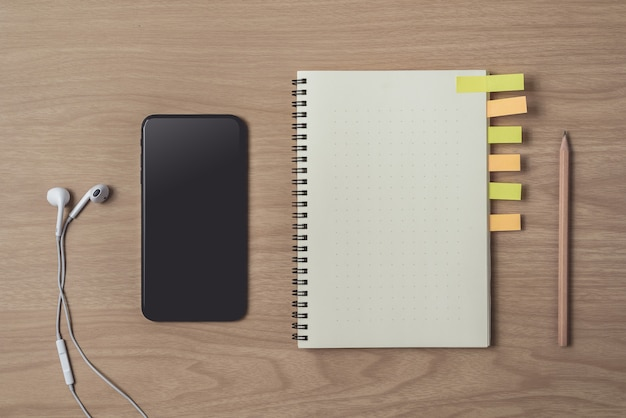 Area di lavoro con diario o notebook e smart phone, auricolare, matita, note adesive su legno Foto Premium