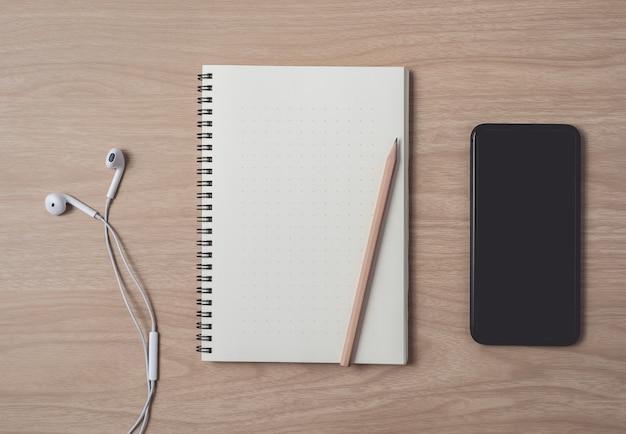 Area di lavoro con diario o notebook e smart phone, auricolare, matita, penna su legno Foto Premium