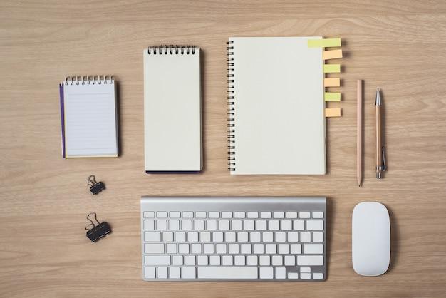 Area di lavoro con diario o taccuino e appunti, mouse, tastiera, matita, note adesive Foto Premium