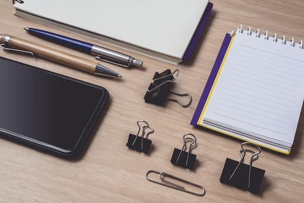 Area di lavoro con diario o taccuino e appunti, smart phone, penna su legno Foto Premium
