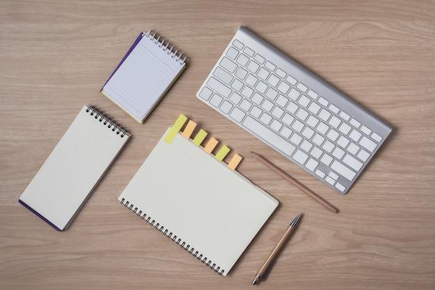 Area di lavoro con diario o taccuino e appunti, tastiera, matita, foglietti adesivi Foto Premium