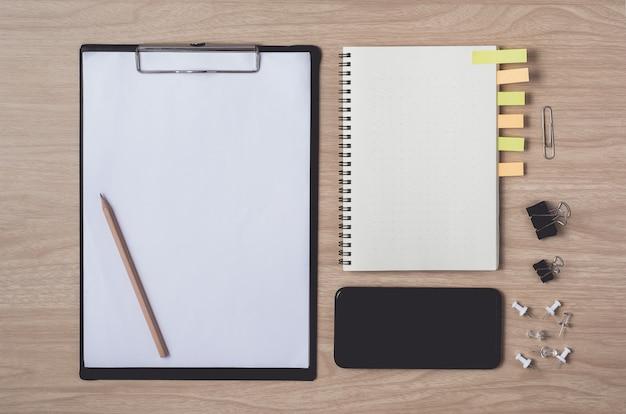 Area di lavoro con diario o taccuino e smart phone, appunti, matita, bigliettini su legno Foto Premium