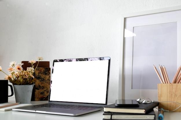 Area di lavoro di mockup loft, laptop schermo vuoto e poster mockup al banco bianco. Foto Premium