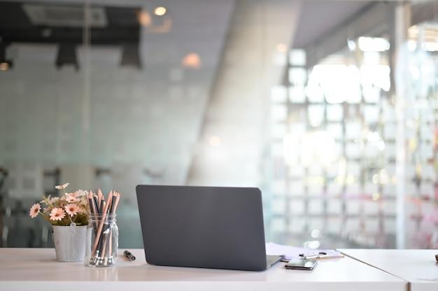 Area di lavoro elegante con computer portatile, forniture per ufficio, fiore in ufficio. concetto di lavoro da scrivania. Foto Premium