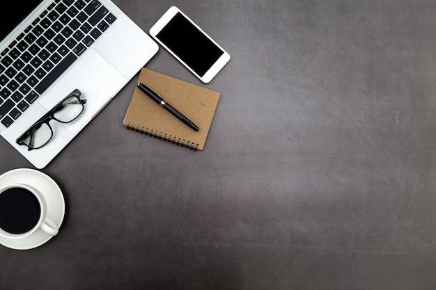 Area di lavoro in ufficio, scrivania nera con quaderno bianco e altre forniture per ufficio. Foto Premium