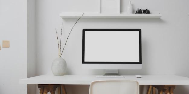 Area di lavoro moderna con il desktop computer dello schermo in bianco e le decorazioni sulla tavola bianca e sulla parete bianca Foto Premium