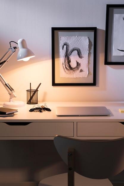 Area di lavoro piacevole e organizzata con lampada Foto Gratuite