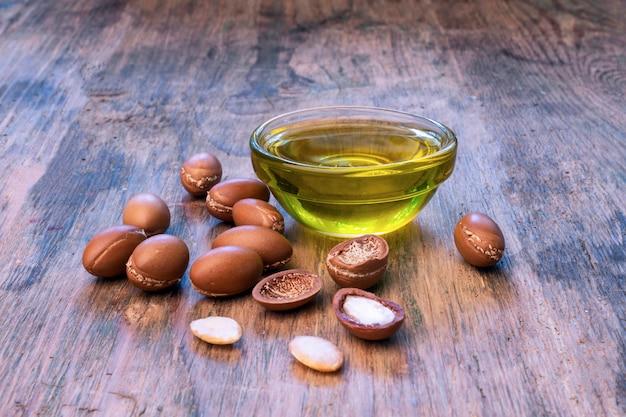 Argan seeds su uno sfondo di legno. olio di argan e argan Foto Premium