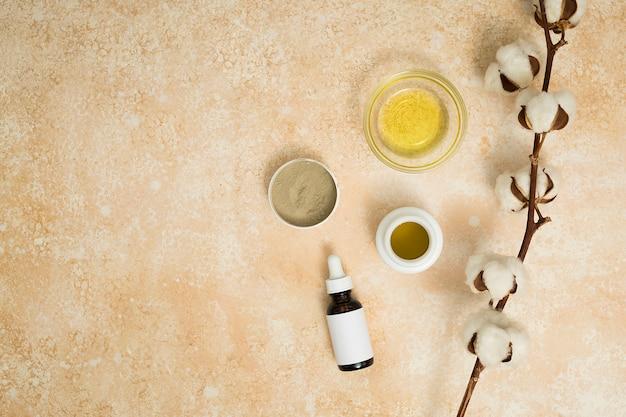 Argilla di rhassoul; miele e oli essenziali con ramoscello di baccello di cotone sul fondale beige Foto Gratuite