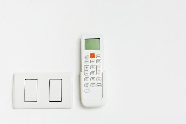 Aria condizionata e interruttore della luce su sfondo bianco con spazio di copia Foto Premium