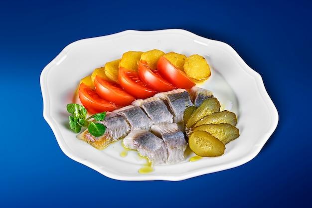 Aringhe norvegesi leggermente salate con patate al forno, pomodori e sottaceti su un piatto bianco. antipasti ucraini classici. Foto Premium