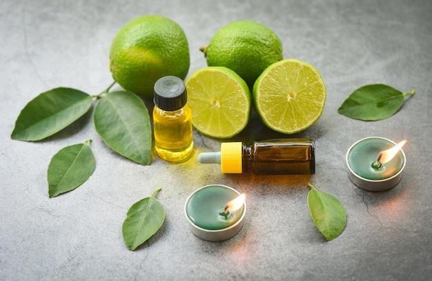 Aromaterapia aroma bottiglie di olio di erbe aromatiche con foglie di limone lime a base di erbe con formulazioni di candele vista dall'alto, oli essenziali naturali su foglia piatta nera e verde Foto Premium