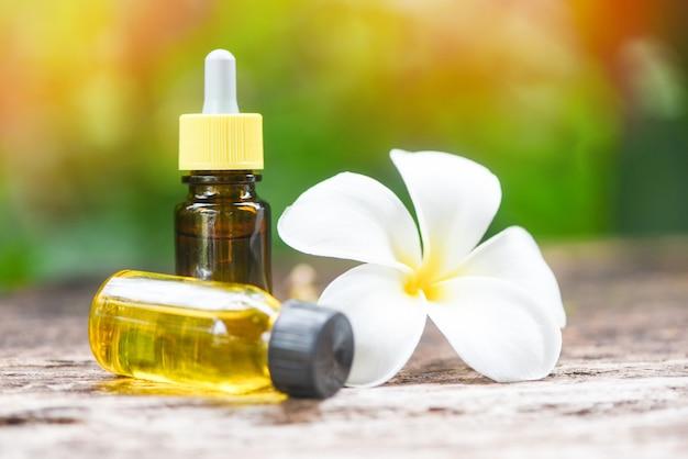 Aromaterapia aroma di bottiglie di olio alle erbe con fiore bianco frangipani plumeriaon con sfondo di natura - oli essenziali naturali sul tavolo di legno e spa minimalista organico Foto Premium