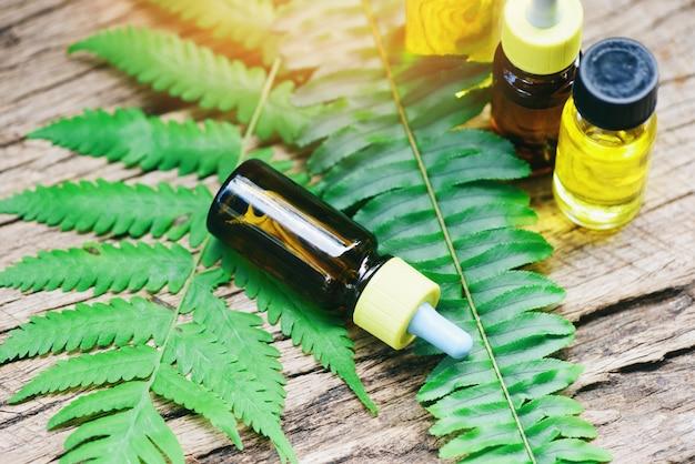 Aromaterapia aroma di bottiglie di olio alle erbe con foglie di felce formulazioni a base di erbe tra cui fiori di campo ed erbe su legno - oli essenziali naturali su foglie di legno e verde biologico Foto Premium