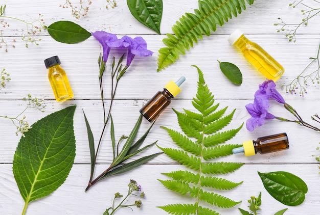 Aromaterapia aroma di bottiglie di olio di erbe con foglie di fiori formulazioni a base di erbe tra cui fiori di campo ed erbe su legno Foto Premium