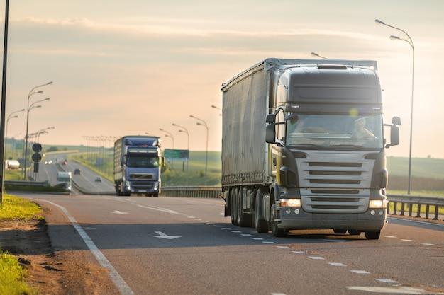Arrivando camion bianco sulla strada in un paesaggio rurale al tramonto Foto Premium