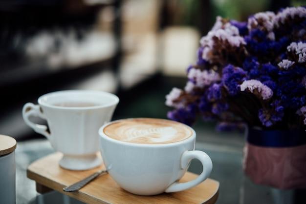 Arte calda del latte in tazza di caffè sulla tavola di legno in caffetteria Foto Gratuite