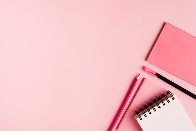 Articoli per ufficio rosa su superficie colorata Foto Gratuite