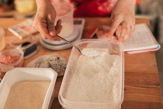 Artigiana femminile che prende la polvere di colore di ceramica con il cucchiaio dal contenitore Foto Gratuite