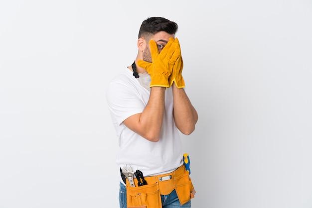Artigiani o elettricista uomo sopra isolato muro bianco che copre gli occhi e guardando attraverso le dita Foto Premium