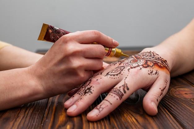 Artista che fa mehndi sulla mano della donna sul tavolo Foto Gratuite