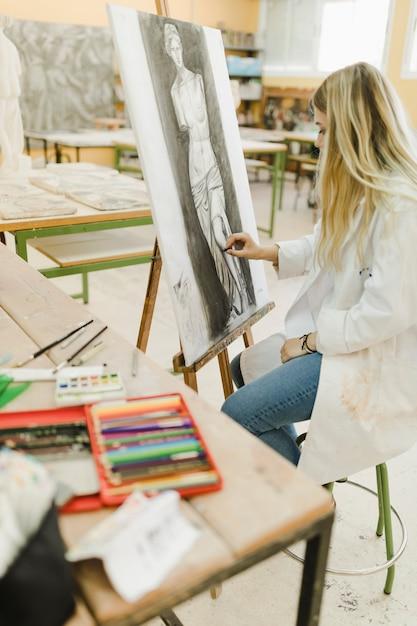 Artista creativo che si siede sullo sgabello che abbozza sul cavalletto con il pastello nero Foto Gratuite
