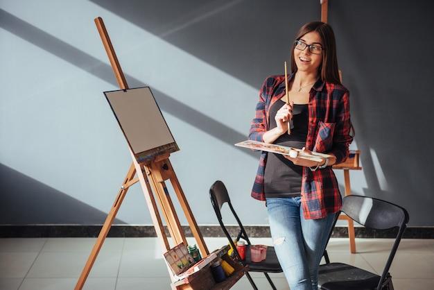 Artista della giovane donna che dipinge un'immagine Foto Premium
