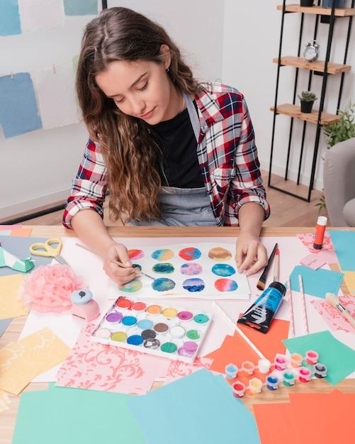 Artista donna dipinto cerchio astratto su carta bianca Foto Gratuite