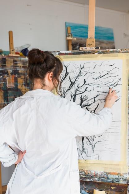 Artista femminile che disegna in modo creativo su tela con carboncino Foto Gratuite