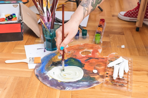 Artista immergendo pennello in vernice Foto Gratuite