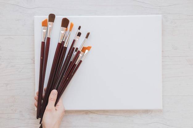 Artista irriconoscibile che tiene pennelli e carta bianca Foto Gratuite