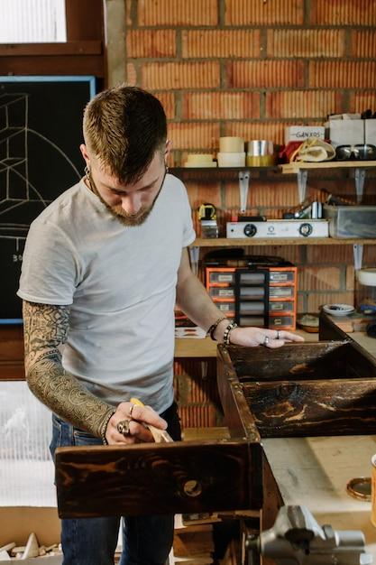 Artista tatuato che applica la vernice della vernice su una mobilia di legno all'officina del mestiere Foto Premium