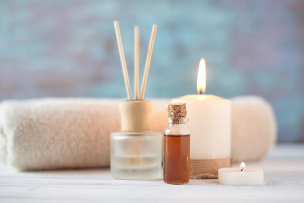 Asciugamani, candela e massaggio olio sul tavolo bianco Foto Premium