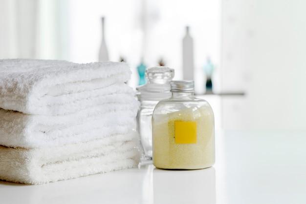 Asciugamani da bagno bianchi e una bottiglia di polvere spa