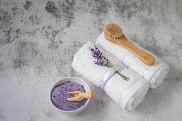 Asciugamani da bagno intrecciati con sale da bagno e spazzola su grigio chiaro. asciugamano spa e set di accessori da bagno contro una parete strutturata. minimalismo, soft focus. spa. Foto Premium