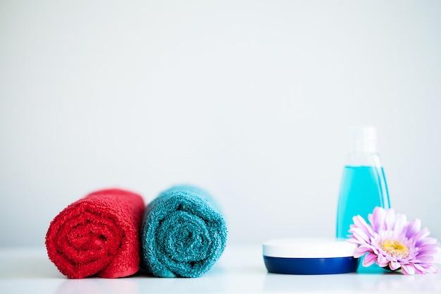 Asciugamani e gel della doccia sulla tavola bianca sul bagno. Foto Premium