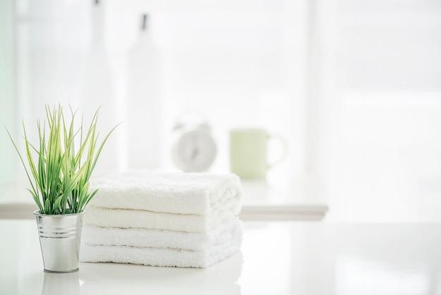 Asciugamani sul tavolo bianco con lo spazio della copia su sfondo sfocato bagno Foto Premium