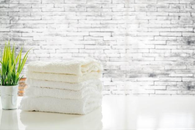 Asciugamani sulla tavola bianca con lo spazio della copia sul vecchio fondo vago del muro di mattoni Foto Premium